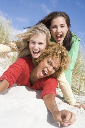 highlights: Tres mujeres posando sobre una colina de arena