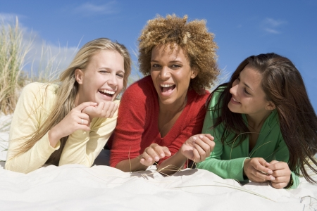 Three women posing on a sand hill photo