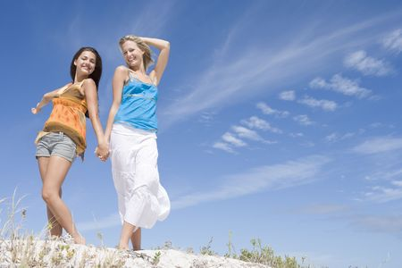 enjoy space: Two young women posing on a sand hill