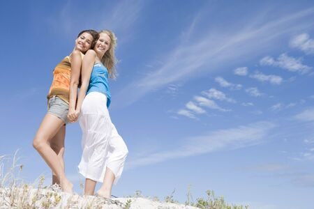 best friends girls: Two young women posing on a sand hill