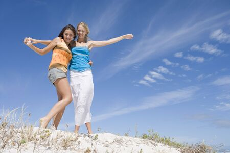blond streaks: Two young women posing on a sand hill
