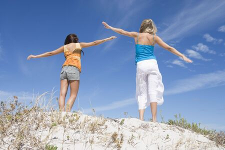 only teenage girls: Two young women posing on a sand hill