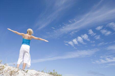 low angle views: Joven mujer posando sobre una colina de arena  Foto de archivo
