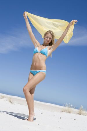 two piece swimsuits: Young woman posing with a scarf on a beach