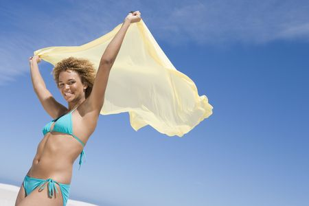 attired: Young woman posing with a scarf on a beach