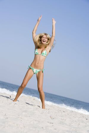 scanty clothing: Woman in a two piece bathing suit posing on a beach Stock Photo