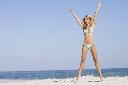 attired: Woman in a two piece bathing suit posing on a beach Stock Photo