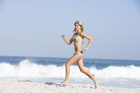 two piece bathing suit: Woman in a two piece bathing suit running on a beach