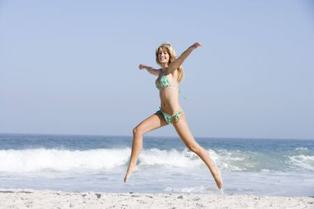scanty clothing: Woman in a two piece bathing suit running on a beach