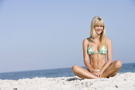 two piece swimsuits: Young woman sitting on a beach