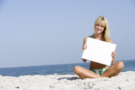 looking towards camera: Woman holding a blank card on a beach Stock Photo