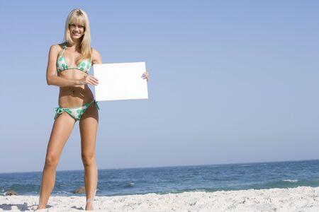 two piece bathing suit: Mujer la celebraci�n de una tarjeta en blanco en una playa