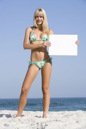 two piece swimsuits: Woman holding a blank card on a beach Stock Photo