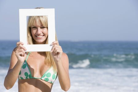 attired: Woman on a beach holding a frame to her face Stock Photo