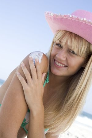 Woman on beach applying sunblock lotion to her shoulder Stock Photo - 3207693