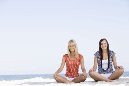 blond streaks: Two women sitting and meditating on a beach