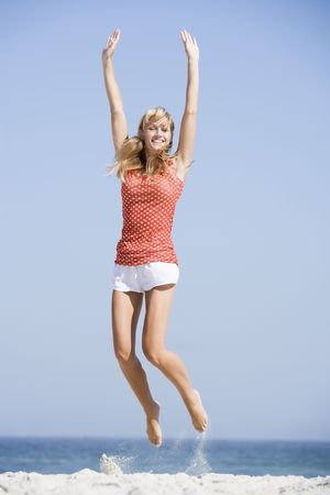 blond streaks: Woman jumping on a beach Stock Photo