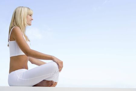 Woman sitting and meditating outdoors photo