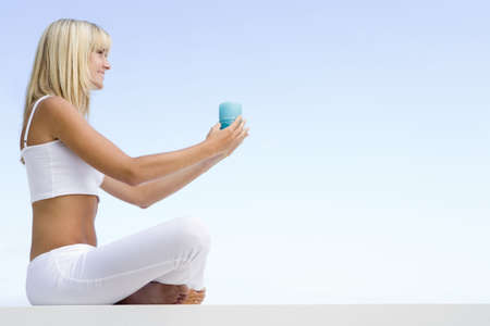blond streaks: Woman sitting and meditating outdoors while holding a candle