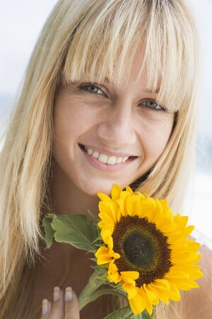 looking towards camera: Woman holding a sunflower