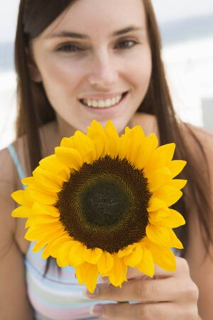 offset angles: Woman holding a sunflower