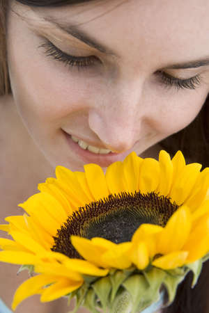 Woman holding and smelling a sunflower Stock Photo - 3204797