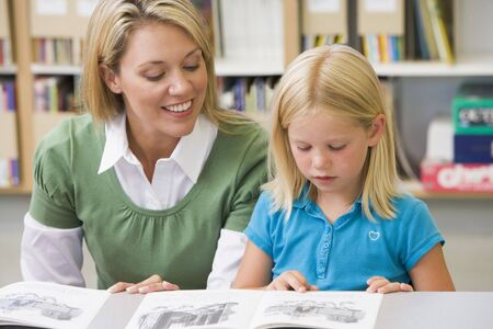 literacy instruction: Student in class reading with teacher