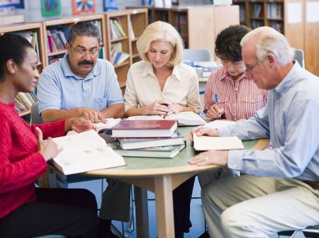 male senior adult: Five people sitting in library with books and notepads (selective focus)