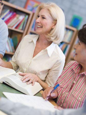 menschen sitzend: Drei Menschen sitzen in der Bibliothek mit B�cher und Notizbl�cke (selektive Fokus)