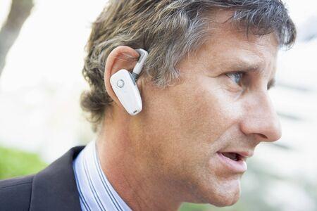 Businessman wearing earpiece outdoors photo