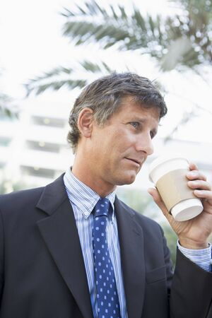 Businessman outdoors drinking coffee photo