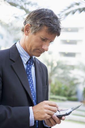 personal digital assistant: Businessman outdoors using personal digital assistant