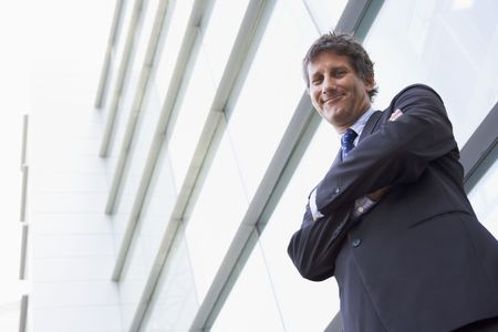 Businessman standing outdoors by building smiling photo