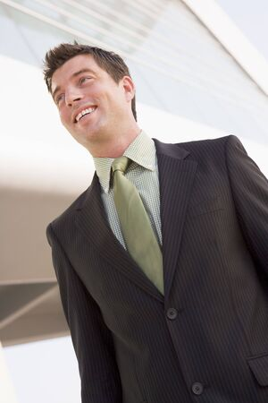 offset view: Businessman standing outdoors by building smiling
