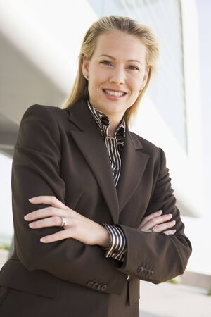 early thirties: Businesswoman standing outdoors by building smiling Stock Photo