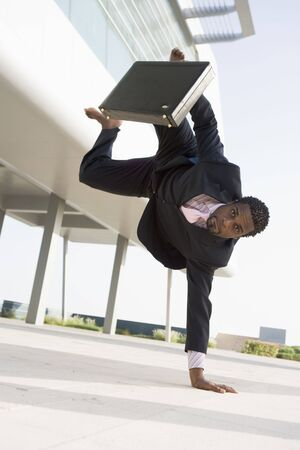 offset view: Businessman outdoors by building standing on one hand
