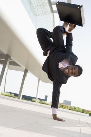 flexible: Businessman outdoors by building standing on one hand smiling