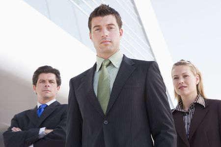 Three businesspeople standing outdoors by building photo
