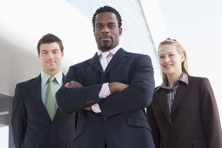 Three businesspeople standing outdoors by building smiling photo