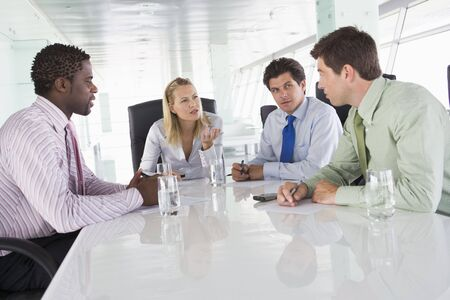 Four businesspeople in a boardroom talking photo