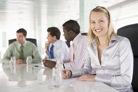 Four businesspeople in a boardroom smiling photo