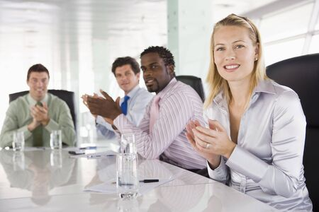 Four businesspeople in a boardroom applauding photo