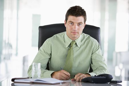 Businessman sitting in office with personal organizer photo