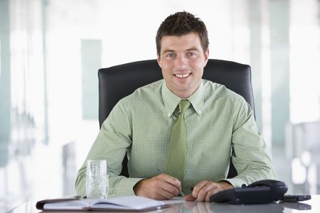 Businessman sitting in office with personal organizer smiling photo