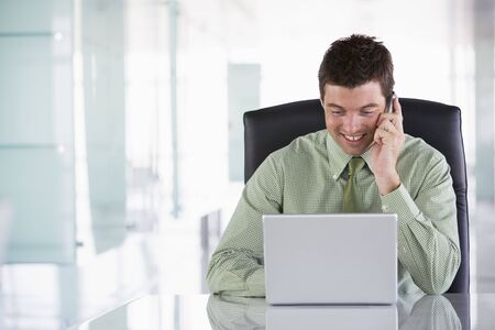 Businessman sitting in office using cellular phone and laptop Stock Photo - 3460114