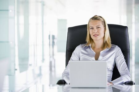 schedulers: Businesswoman in office with a laptop