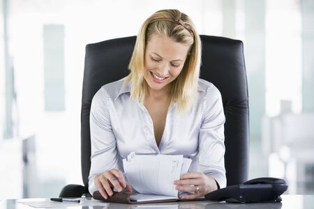 Businesswoman in office looking at personal organizer smiling photo