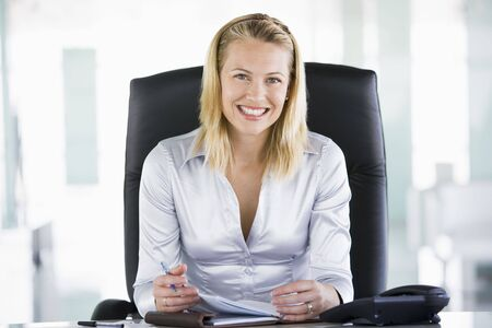 Businesswoman in office with personal organizer smiling photo