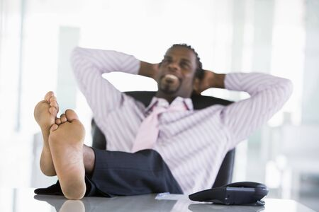 break up: Businessman sitting in office with feet on desk relaxing and smiling Stock Photo