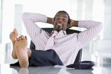 office break: Hombre de negocios sentado en la oficina con los pies sobre la mesa de relajaci�n y sonriente